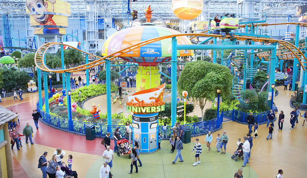 Nickelodeon Universe theme park with a roller coaster, and lots of pepole walking around