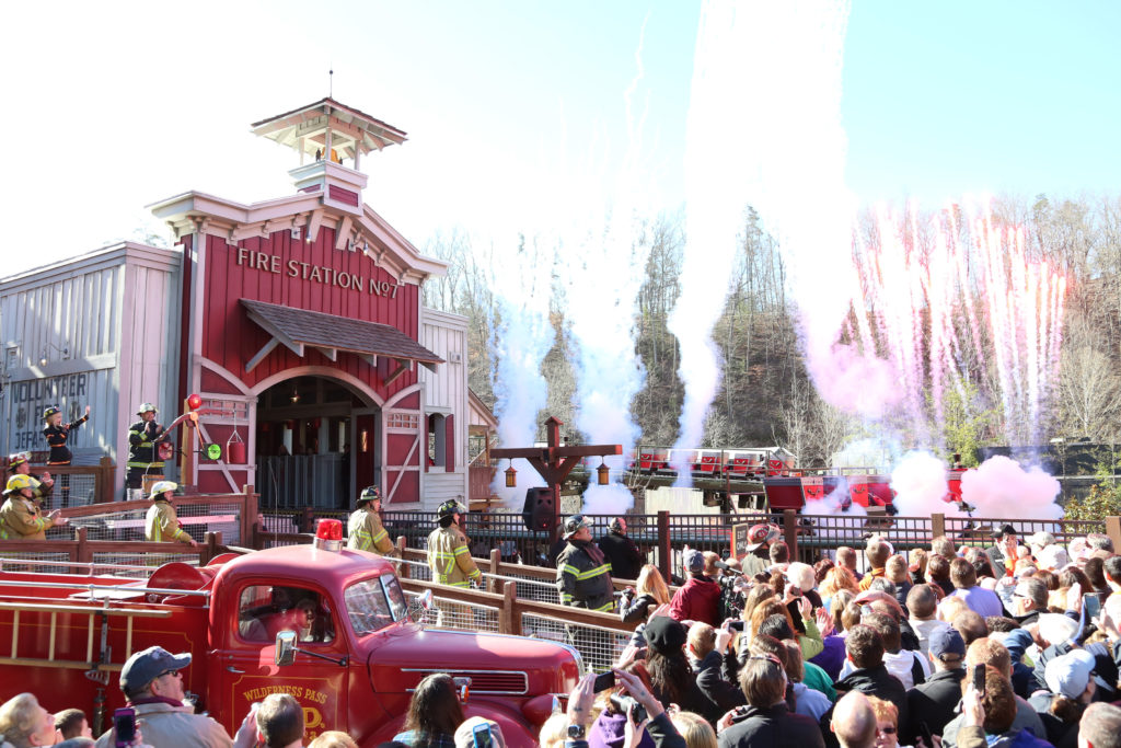 People line up outside fire station with red truck waiting to ride roller coaster